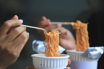 young woman hand holding plastic fork of instant noodles, Sodium diet high risk kidney failure.