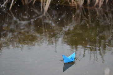 Winter stream with blue paper boat