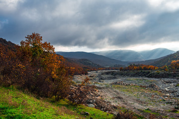 Gray clouds over autumn mountain forest
