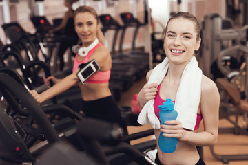Mother and daughter drinking water on treadmill in gym. They look happy, fashionable and fit.