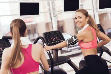 Woman and girl running on treadmill at the gym. They look happy, fashionable and fit.