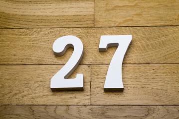 Figure twenty-seven on a wooden, parquet floor.