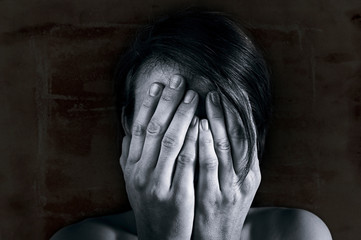 Concept of fear, shame, domestic violence. Woman covers her face by hands on dark background. Black and white image.