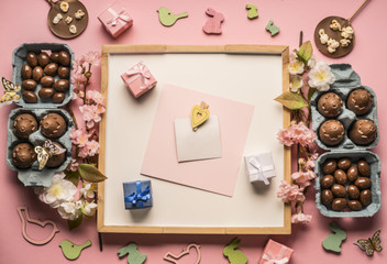 Easter composition with chocolate eggs, spring flowers,  various decorations, wooden rabbits and birds, small gifts on a pink background, space for text, top view