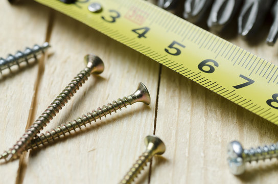 screws and tape measure on wood background, close-up