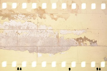 Grunge dripping cracked film strip frame in sepia tones. Damaged brick wall surface.