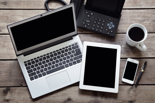 Open laptop with white digital tablet and smartphone on desk from above