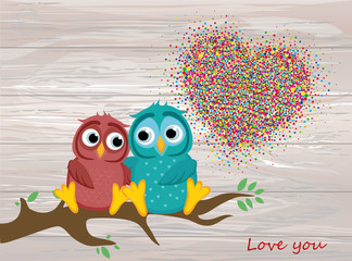 A pair of lovely owls in love, sit on a branch. Colorful confetti