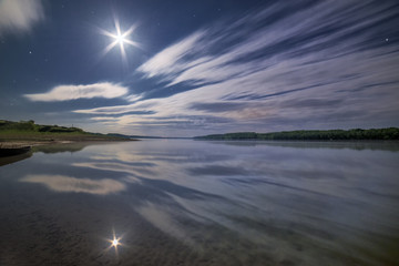 Clouds reflecting in the water under moonlight