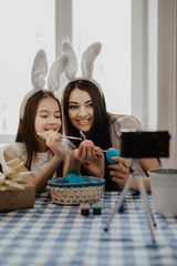Mother and daughter making selfie while decorating Easter eggs at home