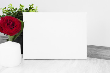 Mock up poster  with red rose. Blank canvas template. White interior on background.