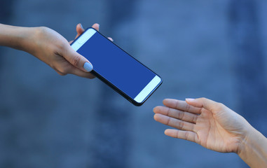 woman hand holding smartphone with blank screen to her friend