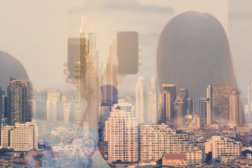 Double exposure of Woman Using a Smart Phone and city background, Communication technology concept
