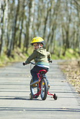 Little child boy cycling on bicycle in green park outdoor in spring. A child is riding a children's bike with support training wheels wearing safety helmet