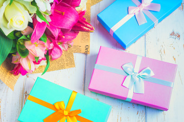 Gift in a box and a bouquet of flowers on a white wooden table. Birthday party.