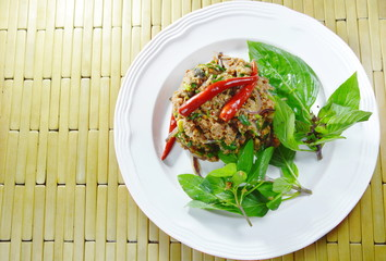 spicy minced catfish with herb topping red chili Thai salad on plate