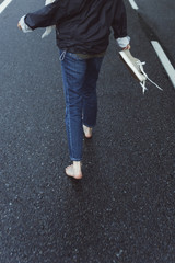 Close up of a woman running bare foot on a wet road