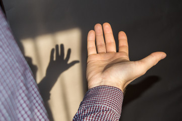 The young man holds an empty hand with his palm up, a shadow on the wall