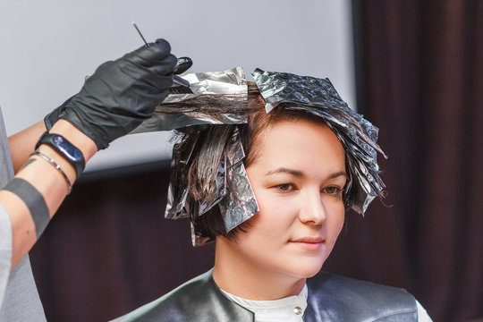 hairdresser coloring client woman hair in beauty barber studio salon, using brush and foil, professional dye and treatment concept
