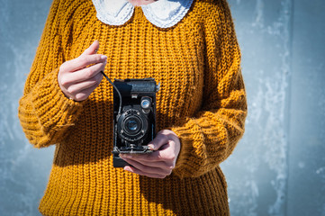Close-up of young woman's hands holding and photographing with an old  vintage  film camera