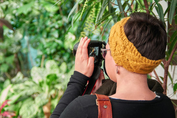 Concept - photography on an excursion. Woman with glasses is taking pictures looking at camera screen. Back view.