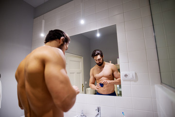 Muscular bearded shirtless man holding hair cosmetics for making hairstyle in front of a mirror in the bathroom.