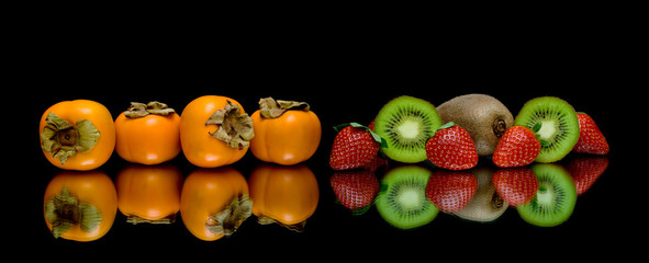persimmon, kiwi and strawberries on a black background
