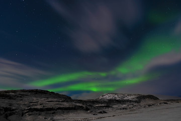 Northern Lights over snow capped mountains in southern Iceland