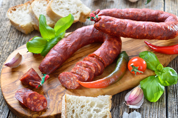 Spanische Spezialität: Luftgetrocknete scharfe Chorizo Paprikasalami auf Olivenholzbrett serviert – Spanish salami: Spicy chorizo sausage with tomatoes and basil served on an olive wood cutting board
