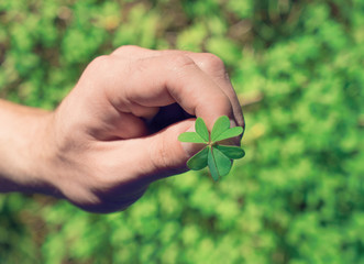 Man's hand holds green leaf of clover. St.Patrick 's Day concept, toned, selective focus