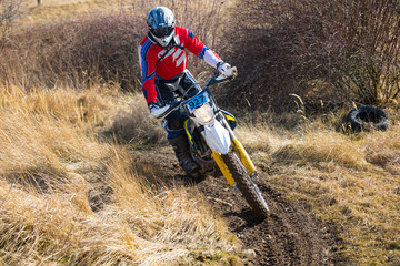 Motocross rider in action on the off-road in nature next to small czech town Pribram, Czech republic