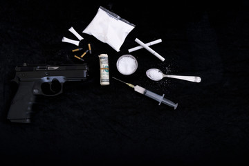Buy drugs.The gun is on the table. have moneys, drugs and syringe on the black cloth. crime, stray, cartridge, dark side, drugs, selected focus.