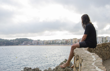 Young male beard, long hair wearing casual clothes sitting on a rock looking into the distance on a Lloret de Mar, Costa Brava, Catalonia, Spain on the background.