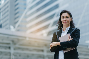 Caucasian businesswoman with wireless tablet standing outdoors with office building in the background