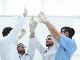 surgical team raising their hand