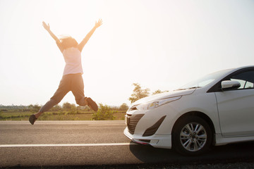 Asian woman happy jump with car on road and sunlight