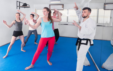 Foto op Aluminium Vechtsport Young adult trainees practicing in karate class