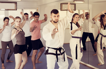 Adults trying new martial moves at karate class