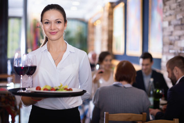 Professional waitress holding serving tray for restaurant guests