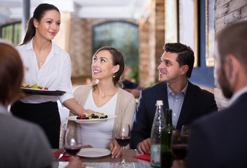 Waitress with dishes serving man and female
