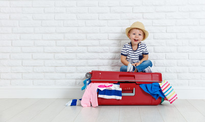 concept travel. happy funny boy child with suitcase