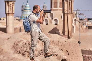 Solo tourist photographs an ancient city in the middle east.