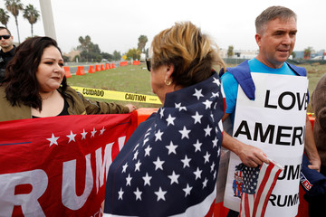 Pro and anti Trump supporters talk as they wait for the arrival of U.S. President Donald Trump to view border wall prototypes in San Diego