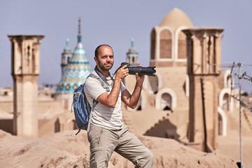 An independent traveler makes a photo, Kashan ancient town, Iran.