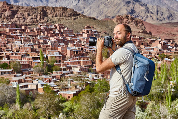 Tourism in Iran, solo traveler photographs the village of Abyaneh.