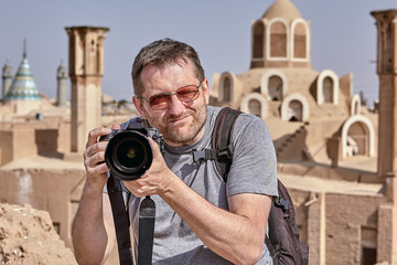 Tourist with a camera photographing an ancient city, Kashan, Iran.