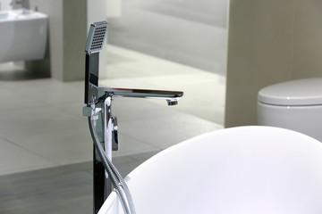 Wanna z kranem, bidetem i muszlą klozetową we współczesnej łazience.