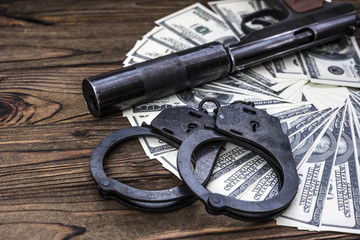 a pistol with a silencer, handcuffs, lies on a dollar money banknote. killer, arrest suspect, prison court law, crime and punishment. weapons