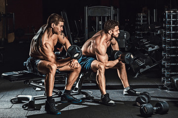 two men bodybuilders execute exercise with dumbbells for biceps sitting in dark gym looking in the mirror