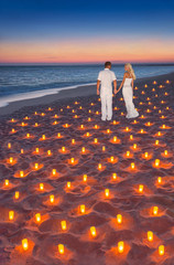 Loving couple at tropical sunset ocean sandy beach with lot of candles lights. Proposal, wedding, valentines day or honeymoon vertical background concept.